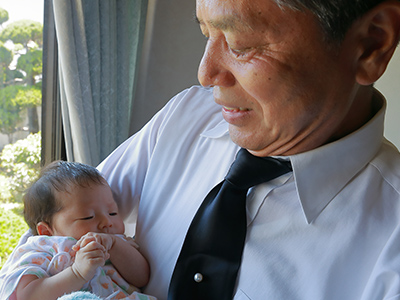 孫を抱きかかえる中高年男性